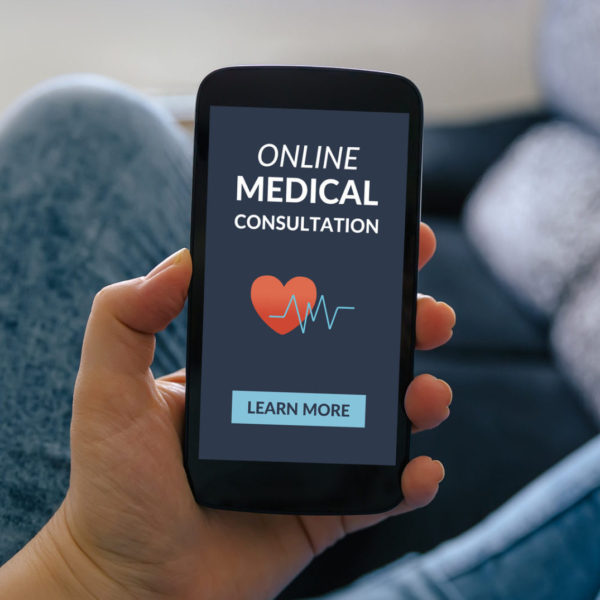 Hand holding smartphone with online medical consultation concept on screen